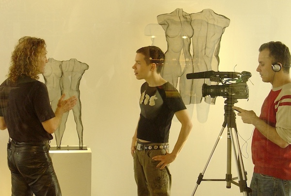 Interviewer asks sculptor in front of his work